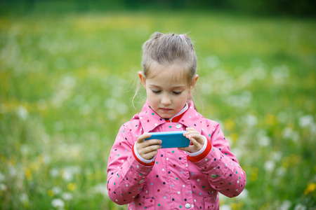 active lifestyle: Little girl checking and reviewing photos she made with smart phone camera, enjoying her time on a dandelion meadow. Active lifestyle, curiosity, pursuing a hobby, technology and kids concept.