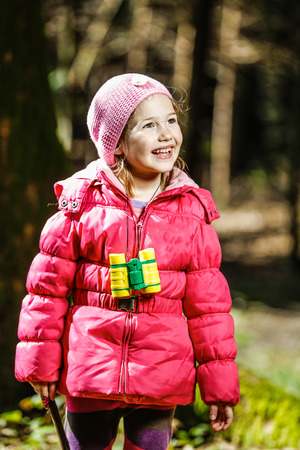 timid: Little girl with binoculars, enjoying sun during walk in the forest, exploring nature, being impish and timid for camera. Active outdoor lifestyle concept. Stock Photo