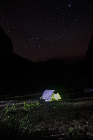 montane: Night landscape with lone, populated and lit easy-to-pitch (pop-up) tent standing on a mountain pasture under the starry sky. Outdoor lifestyle and sleeping under stars concepts and background.