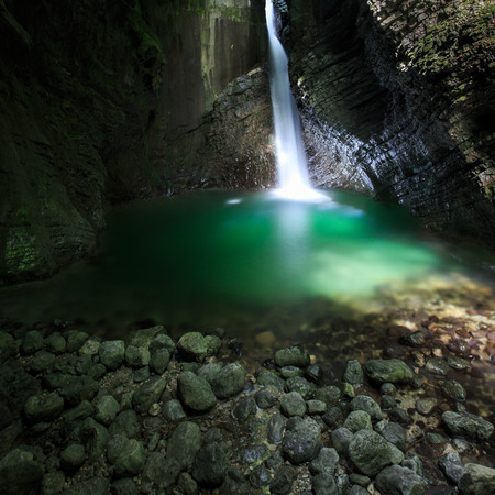 crevasse: Hidden romantic waterfall flowing through a crevasse falling deep into a narrow gorge forming green lake lit by narrow sunray penetrating to the canyon. Pristine nature and geodiversity concept.