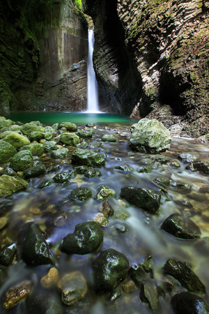 pristine: Alpine spring with romantic waterfall falling deep into a narrow gorge forming a small green pond lit by sunray penetrating to the canyon. Pristine nature and geodiversity concept. Stock Photo