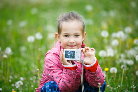pursuing: Little smiling girl proudly showing her photograph on a camera display, taken in a dandelion meadow. Active lifestyle, curiosity, pursuing a hobby, technology and kids concept.