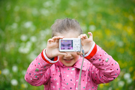 upclose: Little cheerful girl taking a selfie with digital camera, enjoying her time on a dandelion meadow. Active lifestyle, curiosity, pursuing a hobby, technology and kids  concept. Stock Photo