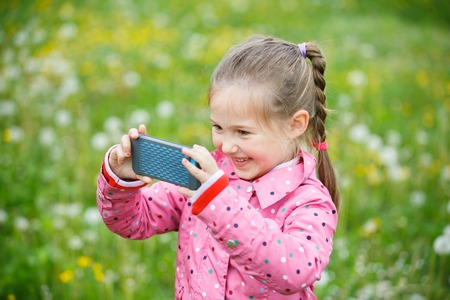 person outdoors: Little smiling and curious girl photographing with her smart phone, exploring nature and standing in a dandelion meadow. Active lifestyle, curiosity, pursuing a hobby, technology and kids concept.