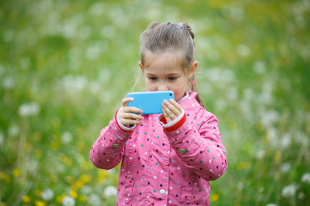 pursuing: Little curious girl photographing with her smart phone, exploring nature and standing in a dandelion meadow. Active lifestyle, curiosity, pursuing a hobby, technology and kids concept.