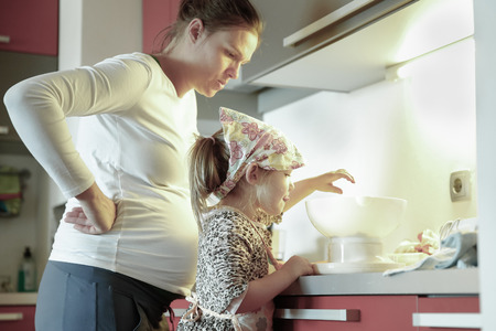 casual woman: Pregnant mother and her daughter spending quality time together in the kitchen, weighing ingredients for birthday cake, having fun. Family values, learning through experience concept.