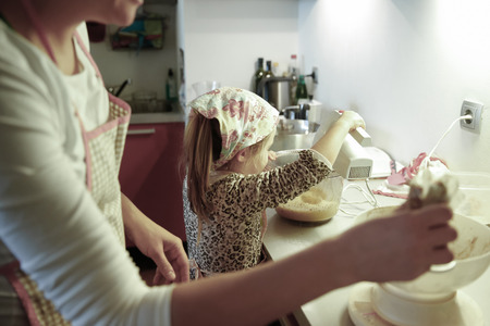 messy kitchen: Mother and little girl spending quality time together in the kitchen, weighing and mixing ingredients for birthday cake, having fun. Family values, learning through inclusion concept.