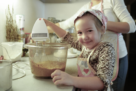 inclusion: Happy little girl mixing dough for a birthday cake, being independent and proud, helping mum in the kitchen. Independence, family values, inclusion, learning through experience concept.
