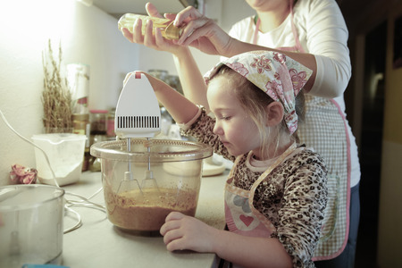 quality time: Mother and daughter spending quality time together in the kitchen, preparing dough for homemade birthday cake. Family values, inclusion, learning through experience concept.