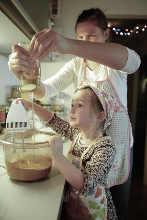 quality time: Mother and daughter spending quality time together in the kitchen, baking for christmas holidays. Family values, inclusion, learning through experience concept.