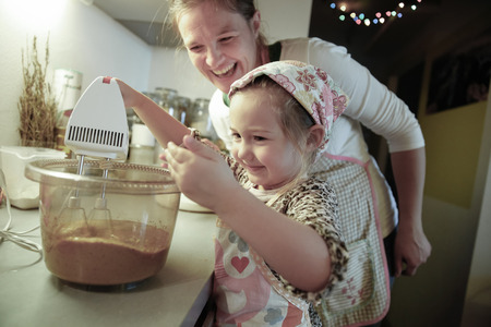 messy kitchen: Mother smiling and tutoring her daughter in the kitchen as she is preparing dough for homemade Christmas cake. Family values, inclusion, learning through experience concept.
