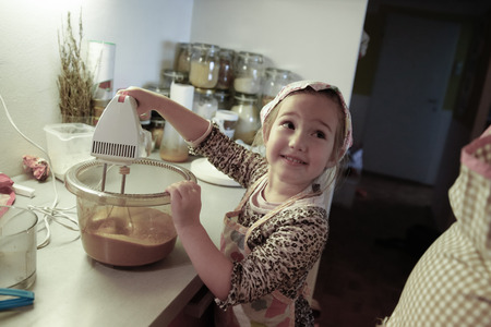 inclusion: Happy little girl mixing dough for a birthday cake, being independent, helping mum in the kitchen. Independence, family values, inclusion, learning through experience concept.