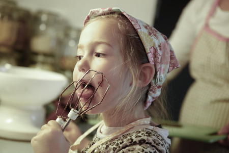 birthday cake: Little girl licking chocolate off the mixer beater after mixing dough for birthday cake. Permissive parenting, learning through experience, child inclusion, homemade food concept.