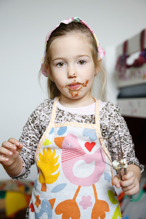 cake mixer: Little girl eating chocolate off the mixer beater after mixing dough for birthday cake. Permissive parenting, learning through experience, child inclusion, homemade food concept.