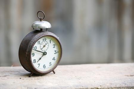 Vintage metalen analoge alarm klok met Arabische cijfers en windup mechanisme, zittend op een houten bank met een retro achtergrond. De tijd is nu, tijd is geld, oude tijden concept.