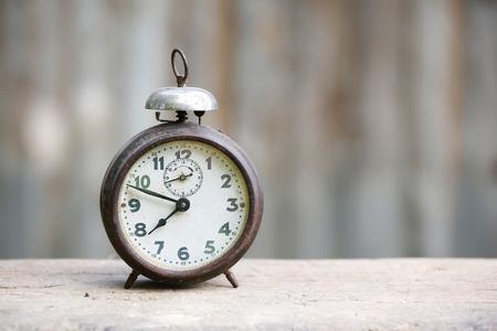 Despertador do vintage de metal analógico com algarismos arábicos e mecanismo de corda, sentado em um banco de madeira com fundo retro. O tempo é agora, o tempo é dinheiro, nos velhos tempos conceito.