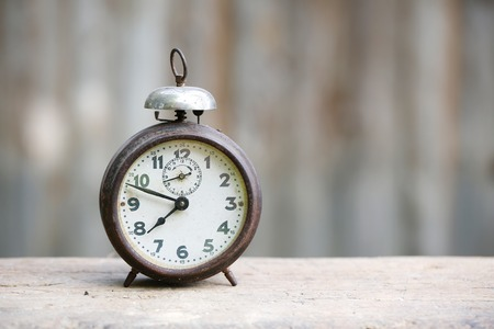 reloj: Reloj de la vendimia de alarma analógica de metal con números arábigos y el mecanismo de cuerda, sentado en un banco de madera con el fondo retro. El tiempo es ahora, el tiempo es dinero, concepto de los viejos tiempos.