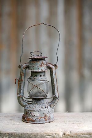 kerosene: Old metallic rusty kerosene lamp with vintage background. Retro nostalgia, home decoration concept. Stock Photo