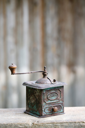 nostalgia: Hand-operated old copper coffee or spices grinder with drawer on vintage background. Retro nostalgia, home decoration concept.