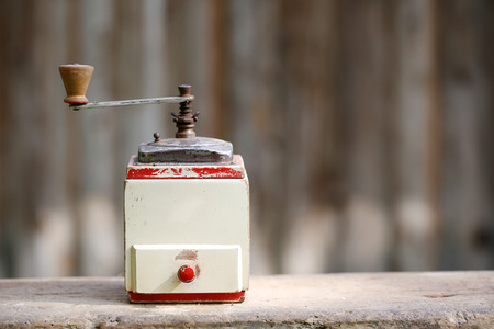 Hand-operated old wooden coffee or spices grinder with drawer on vintage background. Retro nostalgia, home decoration concept. photo