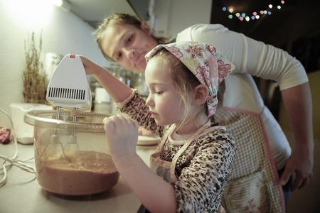 comida: Madre admirar y tutor�a a su hija en la cocina mientras se prepara la masa para pastel de Navidad hecho en casa. Los valores familiares, la inclusi�n, el aprendizaje mediante la experiencia concepto. Foto de archivo