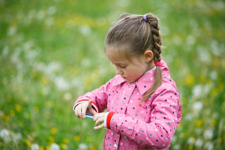 curiosity: Little girl checking and reviewing photos she made with smart phone camera, enjoying her time on a dandelion meadow. Active lifestyle, curiosity, pursuing a hobby, technology and kids concept.
