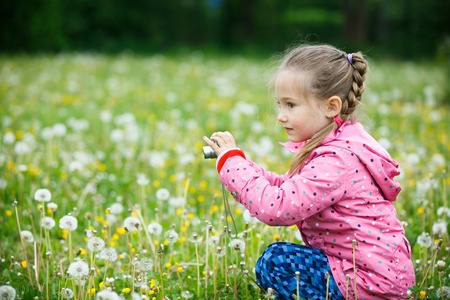 pursuing: Little curious girl photographing with her camera, exploring nature and kneeling in a dandelion meadow. Active lifestyle, curiosity, pursuing a hobby concept. Stock Photo