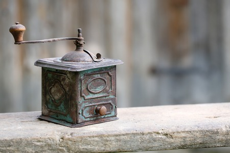 Hand-operated old copper coffee or spices grinder with drawer on vintage background. Retro nostalgia, home decoration concept. photo