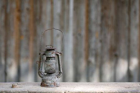 nostalgia: Old metallic rusty kerosene lamp with vintage background. Retro nostalgia, home decoration concept. Stock Photo