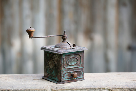 Hand-operated old copper coffee or spices grinder with drawer on vintage background. Retro nostalgia, home decoration concept.