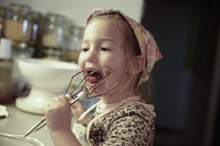 domesticity: Little girl licking chocolate off the mixer beater after mixing dough for birthday cake. Permissive parenting, learning through experience, child inclusion, homemade food concept.