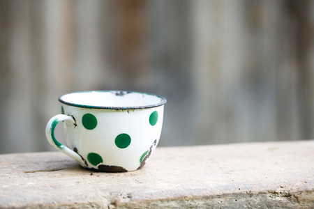 the old times: Charming vintage dotted metal cup covered in decorated enamel rusty on the edges. Home decoration old times retro kitchen concept.