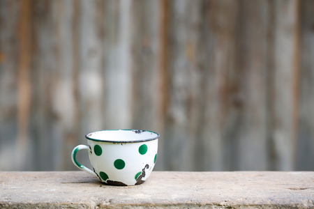 of old times: Charming vintage dotted metal cup, covered in decorated enamel, rusty on the edges. Home decoration, old times, retro kitchen concept.
