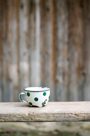 the old times: Charming vintage dotted metal cup, covered in decorated enamel, rusty on the edges. Home decoration, old times, retro kitchen concept.