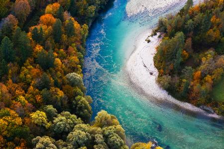 Ongerepte alpine turkooizen rivier meandert door bosrijke landschap in een zonnige herfst dag, luchtfoto. Ongerepte, schone natuur, zuiver water, milieu concept.