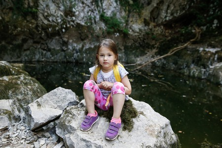 girl scout: Tired but happy little girl resting on a big rock by a small pond, during a forest hike, exploring big nature. Active, healthy and natural lifestyle concept.