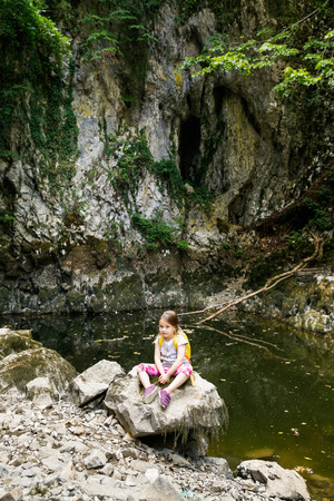 girl scout: Tired and pensive little girl sitting on a big rock by a small pond, during a forest hike, exploring big nature. Active, healthy and natural lifestyle concept.