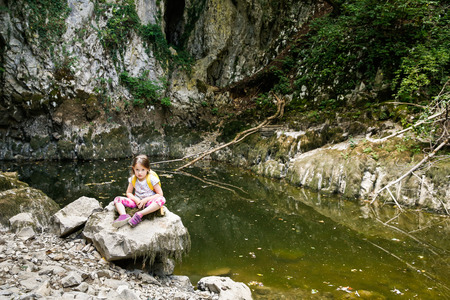 annoyed girl: Tired and annoyed little girl resting on a big rock by a small pond, during a forest hike, exploring big nature. Active, healthy and natural lifestyle concept.