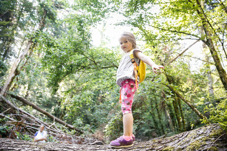 fear child: Proud little girl scout standing on a log in the woods, overcoming fear of heights, with her mother watching in the background. Active, healthy and natural lifestyle concept. Stock Photo