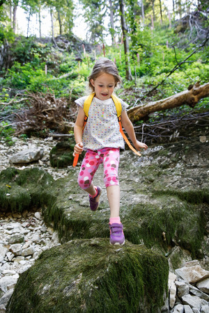 girl scout: Fearless little girl scout jumping over stones in the woods, being courageous and adventurous, exploring and admiring pristine nature. Active, healthy and natural lifestyle concept. Stock Photo