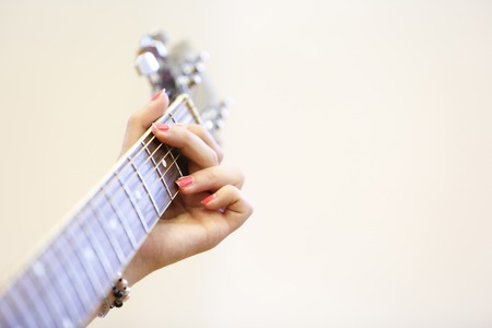 chord: Woman musician holding a guitar, learning, playing a G chord. Self-teaching, artistry, skill concept, musical background.