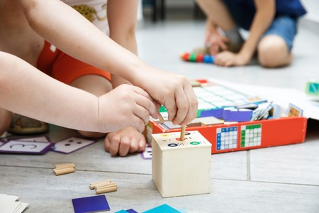ni�os jugando: Ni�os que juegan con hecho en casa, h�galo usted mismo los juguetes educativos. Aprendizaje a trav�s de la experiencia concepto.