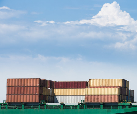 intermodal: Variety of containers, loaded on a cargo ship, prepared for transportation against a blue cloudy sky. Global transportation, global business, globalization, consumerism concept and textured background.