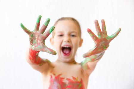 Niña que muestra sus manos, cubierto de pintura de dedos después de pintar un cuadro y su cuerpo con él. Juego sensorial, la crianza permisiva, diversión concepto de infancia, la nitidez selectiva. Foto de archivo