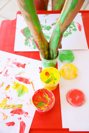 washable: Child dipping fingers in washable, non-toxic finger paints, painting a drawing. Sensory play, innovative approach to learning, fun childhood concept. Stock Photo