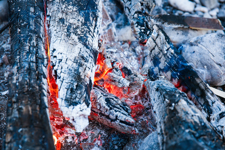 savvy: Embers of a self-made campfire, lit for cooking, roasting and water purification. Safety and survival, outdoor activity concept.