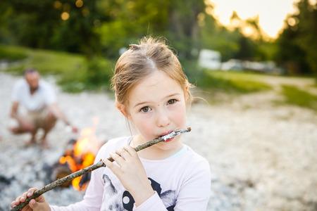 Meisje dat geroosterde marshmallow door een zelfgemaakte kampvuur op familie camping trip, met haar vader op de achtergrond. Actieve natuurlijke levensstijl, leuke familie tijd concept. Stockfoto