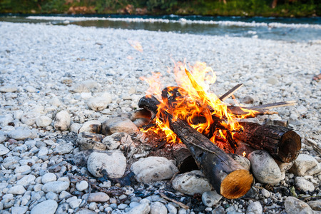 savvy: Self-made campfire by the mountain river, lit for cooking, roasting and water purification. Safety and survival, fun family activity concept.
