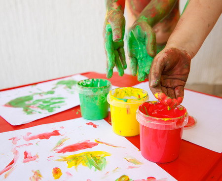 workshop: Children dipping fingers in washable, non-toxic finger paints, painting a drawing. Sensory play, innovative approach to learning, fun childhood concept.