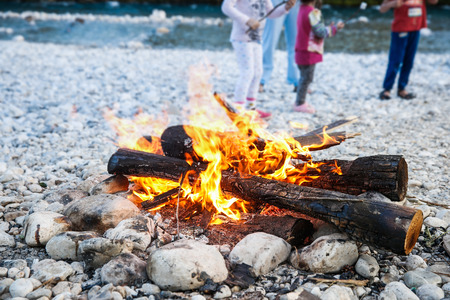 adventure: Family enjoying time by the river and self-made campfire during adventurous camping trip, spending quality time together.  Active natural lifestyle, family time concept.